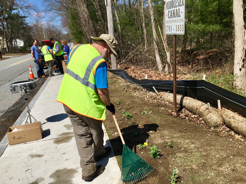 . Brian Henderson of Billerica raked an area on Lowell Street where new flowers were planted by a wayside exhibit by the Middlesex Canal.  Photo by Mary Leach