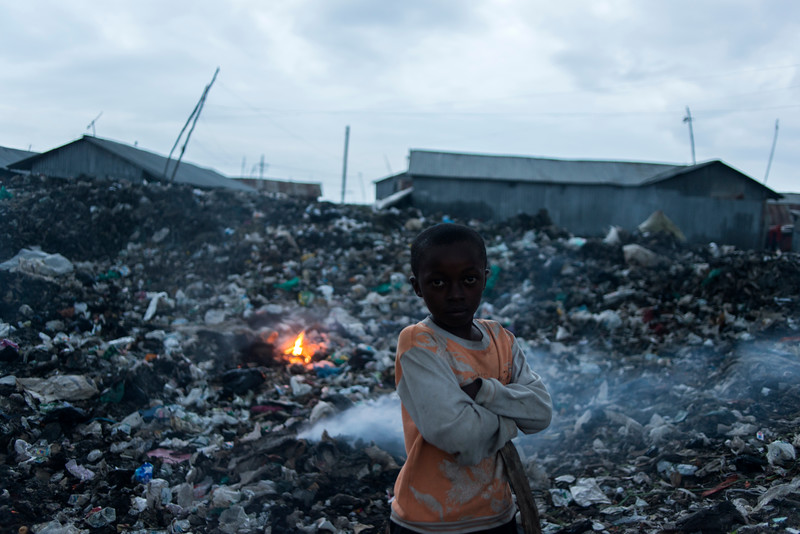 A boy burns his family's garbage in Nairobi's Mukuru Kwa Njenga slum on Friday, May 29, 2015. Irregular trash pick-up and general lack of city sanitation services have contributed to widespread outbreaks of cholera and parasites like jiggers, bedbugs and lice.