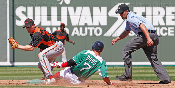 FORT MYERS, FL, March 17, 2012: Umpire Tim Timmons, right, watches as Boston Red Sox batter Cody Ross, center, slides safely into second base with a double ahead of a tag by Baltimore Orioles second baseman Matt Antonelli in the fourth inning of a split-squad Grapefruit League spring training game at JetBlue Park at Fenway South. (Brita Meng Outzen/Boston Red Sox)