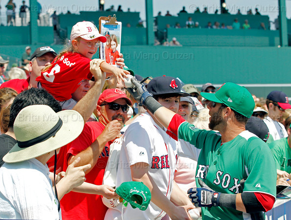 FORT MYERS, FL, March 17, 2012: A young fan, top, gets an autographed baseball from Boston Red Sox second baseman Dustin Pedroia, right, dressed in the team's traditional green St. Patrick's Day uniform jersey and hat, before a split-squad Grapefruit League spring training game against the Baltimore Orioles at JetBlue Park at Fenway South. (Brita Meng Outzen/Boston Red Sox)