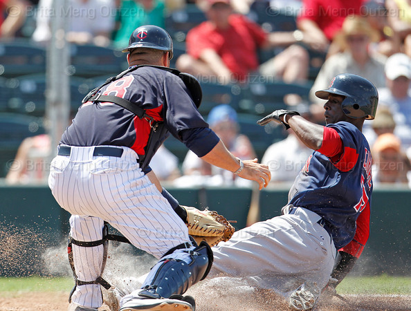FORT MYERS, FL, March 30, 2012: Boston Red Sox base runner Pedro Ciriaco, right, slides home safely as Minnesota Twins catcher Ryan Doumit is late with the tag in the seventh inning of a Grapefruit League spring training game at Hammond Stadium. (Brita Meng Outzen/Boston Red Sox)