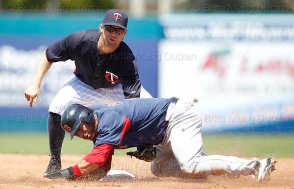 FORT MYERS, FL, March 30, 2012: Boston Red Sox base runner Mike Aviles, bottom, reacts after being tagged out while attempting to steal second base by Minnesota Twins shortstop Brian Dozier in the second inning of a Grapefruit League spring training game at Hammond Stadium. (Brita Meng Outzen/Boston Red Sox)