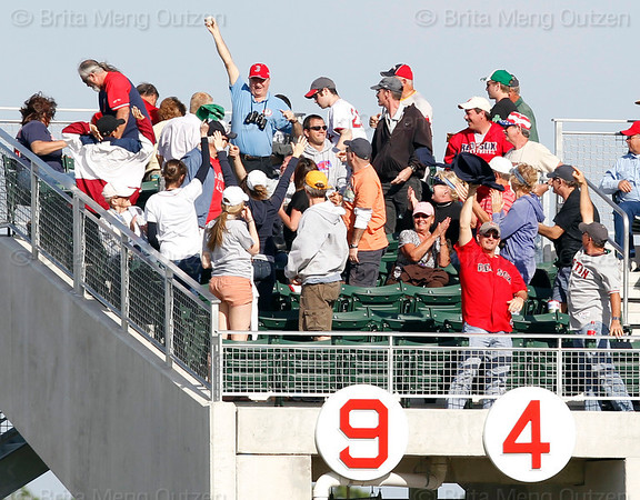FORT MYERS, FL, March 4, 2012: A Boston Red Sox fan in the upper right field deck holds up the baseball hit by Red Sox batter Lars Anderson for a grand slam in the seventh inning of a Grapefruit League game against the Minnesota Twins at JetBlue Park at Fenway South. (Brita Meng Outzen/Boston Red Sox)