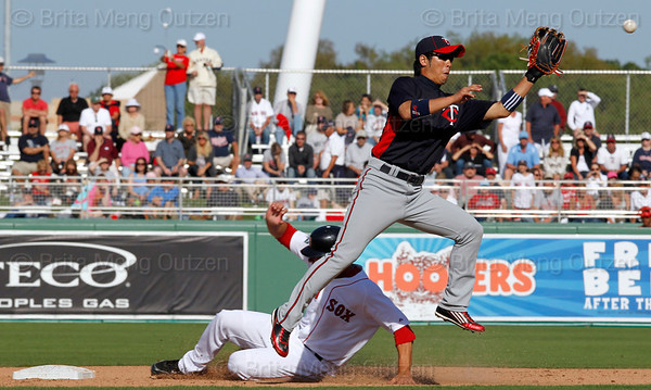 FORT MYERS, FL, March 4, 2012: Boston Red Sox base runner Alex Hassan, left, steals second base as Minnesota Twins shortstop Tsuyoshi Nishioka has to jump for the errant throw in the seventh inning of a Grapefruit League game at JetBlue Park at Fenway South. (Brita Meng Outzen/Boston Red Sox)