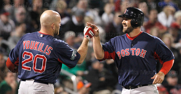 FORT MYERS, FL, March 5, 2012: Boston Red Sox base runner Kelly Shoppach, right, is congratulated by teammate Kevin Youkilis after scoring on a wild pitch by Minnesota Twins pitcher Jason Marquis in the second inning of a Grapefruit League game at Hammond Stadium. (Brita Meng Outzen/Boston Red Sox)