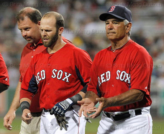 FORT MYERS, FL, March 22, 2012:  Boston Red Sox batter Dustin Pedroia, center, leaves the field with manager Bobby Valentine, right, and head trainer Rick Jameyson after being hit with a baseball thrown by New York Yankees pitcher Adam Warren in the third inning of a Grapefruit League spring training game at JetBlue Park at Fenway South. (Brita Meng Outzen/Boston Red Sox)
