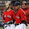 FORT MYERS, FL, March 22, 2012:  Boston Red Sox batter Dustin Pedroia, left, leaves the field with manager Bobby Valentine, center, and head trainer Rick Jameyson after being hit with a baseball thrown by New York Yankees pitcher Adam Warren in the third inning of a Grapefruit League spring training game at JetBlue Park at Fenway South. (Brita Meng Outzen/Boston Red Sox)