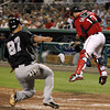 FORT MYERS, FL, March 22, 2012: Boston Red Sox catcher Kelly Shoppach, right, has to jump to corral a throw to the plate as New York Yankees base runner Jose Gil scores in the fifth inning of a Grapefruit League spring training game at JetBlue Park at Fenway South. (Brita Meng Outzen/Boston Red Sox)