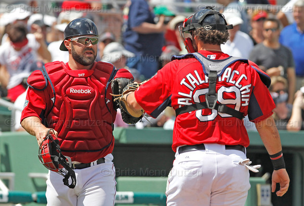 FORT MYERS, FL, March 24, 2012: Boston Red Sox catchers Kelly Shoppach, left, and Jarrod Saltalamacchia bump gloves as Shoppach takes his position behind home plate to start the third inning while Saltalamacchia returns to the dugout after warming up pitcher Alfredo Aceves during a Grapefruit League spring training game against the Philadelphia Phillies at JetBlue Park at Fenway South. (Brita Meng Outzen/Boston Red Sox)