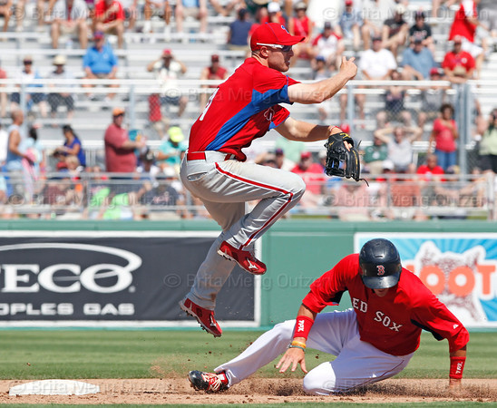 FORT MYERS, FL, March 24, 2012: Philadelphia Phillies shortstop Pete Orr, left, jumps over Boston Red Sox base runner Kobrin Vitek as he throws to first base to complete the double play in the fifth inning of a Grapefruit League spring training game at JetBlue Park at Fenway South. (Brita Meng Outzen/Boston Red Sox)