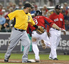 FORT MYERS, FL, March 9, 2012: Boston Red Sox batter Mike Aviles, center, reaches first base ahead of the tag of Pittsburgh Pirates first baseman Jake Fox, left, as Red Sox first base coach Alex Ochoa watches in the seventh inning of a Grapefruit League spring training game at JetBlue Park at Fenway South. Pirates shortstop Chase d'Arnaud was charged with an error on the play. (Brita Meng Outzen/Boston Red Sox)