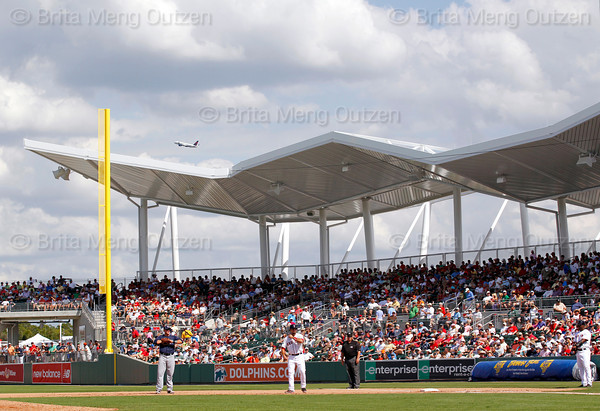 FORT MYERS, FL, March 27, 2012: An airplane departs Fort Myers as Boston Red Sox base runner Kelly Shoppach, center, takes a lead off first base during the seventh inning of a Grapefruit League spring training game at JetBlue Park at Fenway South. (Brita Meng Outzen/Boston Red Sox)