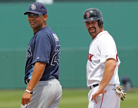 FORT MYERS, FL, March 27, 2012:  Boston Red Sox base runner Kevin Youkilis, right, and Tampa Bay Rays first baseman Carlos Pena react to someone in the Rays dugout between pitches in the second inning of a Grapefruit League spring training game at JetBlue Park at Fenway South. (Brita Meng Outzen/Boston Red Sox)