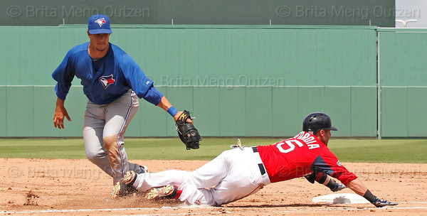 FORT MYERS, FL, March 29, 2012: Boston Red Sox batter Dustin Pedroia, right, dives head-first into first base in an attempt to avoid the tag by Toronto Blue Jays first baseman Yan Gomes in the fifth inning ofa Grapefruit League spring training game at JetBlue Park at Fenway South. (Brita Meng Outzen/Boston Red Sox)
