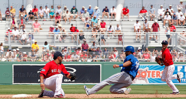 FORT MYERS, FL, March 29, 2012: Boston Red Sox shortstop Mike Aviles, left, waits with the baseball as Toronto Blue Jays base runner Eric Thames, center, is caught stealing at second base in the sixth inning of a Grapefruit League spring training game at JetBlue Park at Fenway South. Red Sox second baseman Dustin Pedroia is at right. (Brita Meng Outzen/Boston Red Sox)