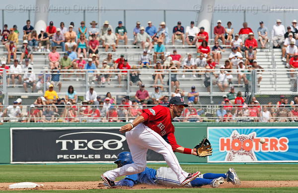 FORT MYERS, FL, March 29, 2012: Boston Red Sox shortstop Mike Aviles, top, waits for the baseball as Toronto Blue Jays base runner Rajai Davis slides into second base with a steal in the sixth inning of a Grapefruit League spring training game at JetBlue Park at Fenway South. (Brita Meng Outzen/Boston Red Sox)