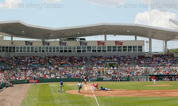 FORT MYERS, FL, March 29, 2012: Toronto Blue Jays base runner Ricardo Nanita, second from right, dives back to first base as Boston Red Sox catcher Kelly Shoppach, center, and first baseman Adrian Gonzalez, third from right, try to pick him off in the third inning of a Grapefruit League spring training game at JetBlue Park at Fenway South. (Brita Meng Outzen/Boston Red Sox)