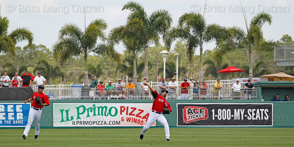 FORT MYERS, FL, March 29, 2012: Boston Red Sox center fielder Jason Repko, right, throws the baseball back to the infield as right fielder Shannon Wilkerson watches after catching a fly ball hit by Toronto Blue Jays Chris Hawkins in the eighth inning of a Grapefruit League spring training game at JetBlue Park at Fenway South. (Brita Meng Outzen/Boston Red Sox)