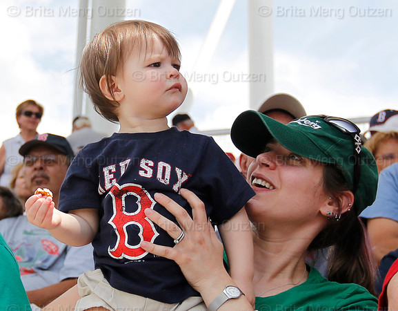 FORT MYERS, FL, March 29, 2012: A young fan being held by his mother watches intently as other fans in the stands try to catch a foul ball in the third inning of a Grapefruit League spring training game between the Boston Red Sox and Toronto Blue Jays at JetBlue Park at Fenway South. (Brita Meng Outzen/Boston Red Sox)