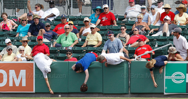 FORT MYERS, FL, March 29, 2012: Boston Red Sox fans reach over the right field wall trying to field a foul ball in the ninth inning of a Grapefruit League spring training game against the Toronto Blue Jays at JetBlue Park at Fenway South. (Brita Meng Outzen/Boston Red Sox)