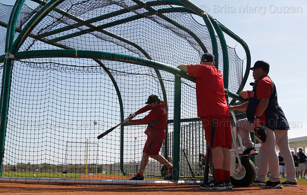 FORT MYERS, FL, Feb. 21, 2012: Boston Red Sox batter Adrian Gonzalez, left, takes batting practice as, from left, teammate Kevin Youkilis, hitting coach Dave Magadan and minor league hitting coordinator Victor Rodriguez watch during an informal workout at Spring Training. (Brita Meng Outzen/Boston Red Sox)
