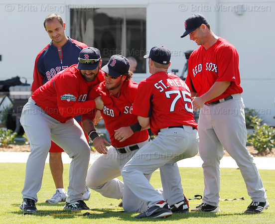 FORT MYERS, FL, Feb. 21, 2012: Boston Red Sox catcher Jarrod Saltalamacchia, center, is helped to his feet in fun by fellow catchers Kelly Shoppach, second from left, Max St. Pierre, second from right, and Daniel Butler after tripping and falling during an agility drill at Spring Training. Red Sox strength and conditioning coach Pat Sandora is at left. (Brita Meng Outzen/Boston Red Sox)