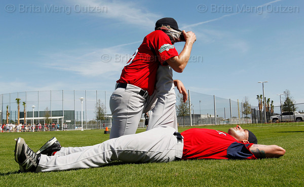 FORT MYERS, FL, Feb. 21, 2012: Boston Red Sox pitcher Rich Hill, left, helps to stretch out fellow pitcher Alfredo Aceves's hamstrings following his workout at Spring Training. (Brita Meng Outzen/Boston Red Sox)