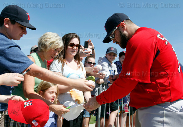 FORT MYERS, FL, Feb. 21, 2012: Boston Red Sox catcher Kelly Shoppach, right, returns an autographed hat to a young fan following his workout at Spring Training. (Brita Meng Outzen/Boston Red Sox)