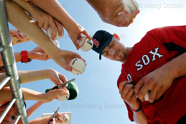 FORT MYERS, FL, Feb. 21, 2012: Fans offer baseballs, hats and bats for Boston Red Sox catcher Ryan Lavarnway (right) to sign after his workout at Spring Training. (Brita Meng Outzen/Boston Red Sox)