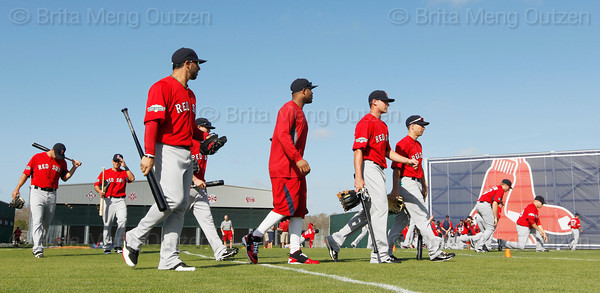 FORT MYERS, FL, Feb. 23, 2012: From left, Boston Red Sox position players Alex Hassan, Che-Hsuan Lin, Mike Aviles, Ryan Sweeney, Carl Crawford, Will Middlebrooks and Nate Spears walk by pitchers and catchers stretching on the agility field at the beginning of their Spring Training workout. (Brita Meng Outzen/Boston Red Sox)