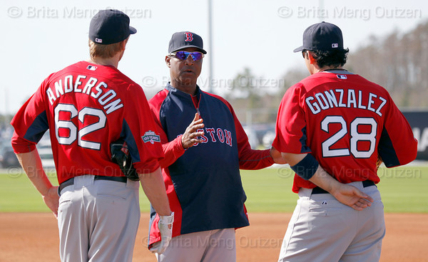 FORT MYERS, FL, Feb. 23, 2012: Boston Red Sox third base coach Jerry Royster, center, talks to first basemen Lars Anderson, left, and Adrian Gonzalez about their role in an pitchers' fielding practice drill at Spring Training workouts. (Brita Meng Outzen/Boston Red Sox)