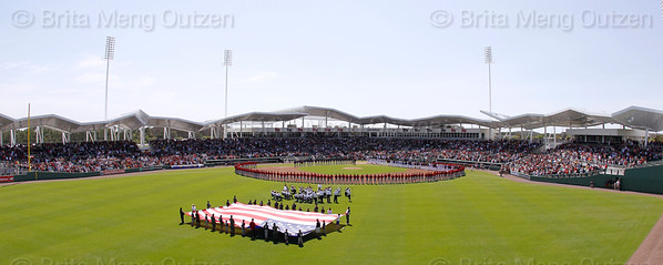FORT MYERS, FL, March 4, 2012: Boston Red Sox and Minnesota Twins players and Red Sox minor leaguers line the infield while Little League players and veterans hold a giant American flag as the Gulf Coast Orchestra plays the National Anthem during the pregame ceremony celebrating Opening Day at JetBlue Park at Fenway South, the new Boston Red Sox spring training home. (Brita Meng Outzen/Boston Red Sox)