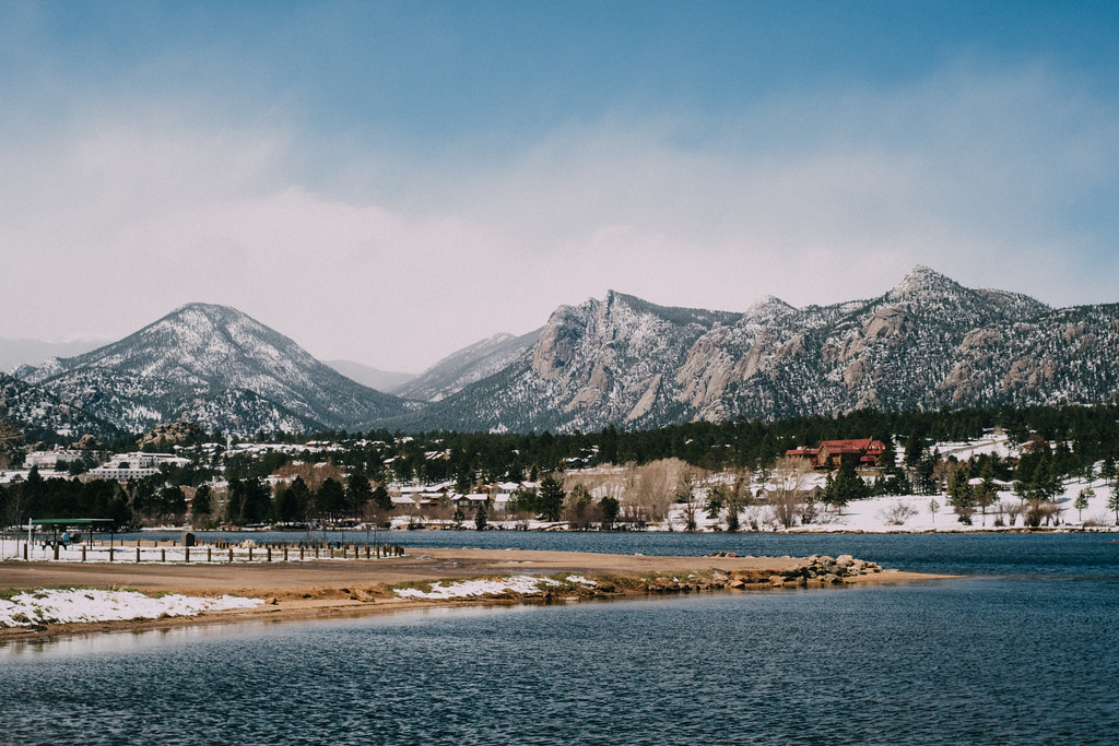 . A dusting of snow covers the peaks behind Lake Estes. (Bob Wooley/Trail-Gazette)
