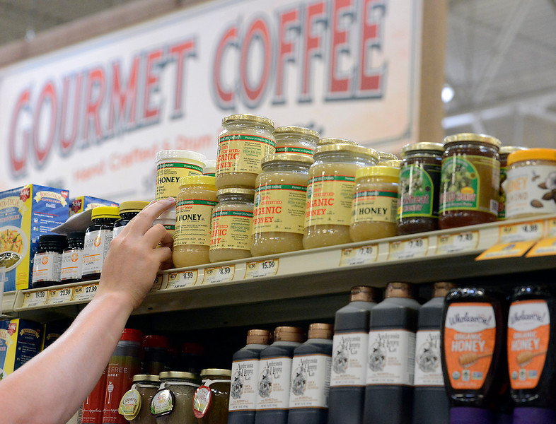 Spouts Farmers Market grocery clerk Mitch Kwan puts honey on the shelves at the new Loveland store on Monday, June 27, 2016, in preparation of their opening day on Wednesday. (Photo by Jenny Sparks/Loveland Reporter-Herald)