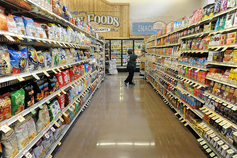 Spouts Farmers Market scan coordinator Flory Maestas scans and adjusts product on the shelves at the new Loveland store on Monday, June 27, 2016, in preparation of their opening day on Wednesday. (Photo by Jenny Sparks/Loveland Reporter-Herald)