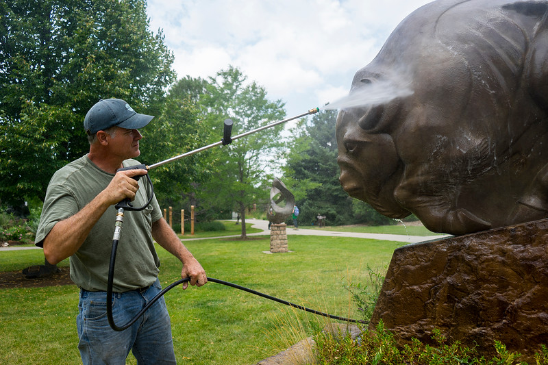 David DeDecker sprays off a sculpture at Benson Sculpture Garden in Loveland on July 28, 2016. The sculptures are power washed before wax is applied to ensure a proper bond that will keep the sculptures clean.<br /> <br /> Photo by Michael Ortiz/ Loveland Reporter-Herald