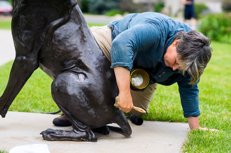 Jo DeDecker waxes a bronze sculpture in the Benson Sculpture Garden in Loveland on July 28, 2016. The wax that is applied will create a protective coating for the artwork that will keep out dirt, water and other contaminants. <br /> <br /> Photo by Michael Ortiz/Loveland Reporter-Herald