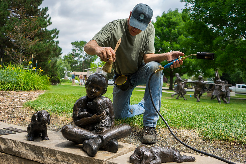 David DeDecker applies wax to a sculpture in Benson Sculpture Garden in Loveland on July 28, 2016. David and his sister Jo have been sculptures for over 25 years across the Midwest.<br /> <br /> Photo by Michael Ortiz/ Loveland Reporter-Herald