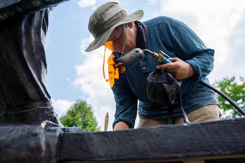 Jo DeDecker waxes a bronze sculpture in the Benson Sculpture Garden in Loveland on July 28, 2016. The bronze sculptures must be heated to soften the existing wax and allow for application of a new wax layer that will keep the artwork clean.<br /> <br /> Photo by Michael Ortiz/Loveland Reporter-Herald