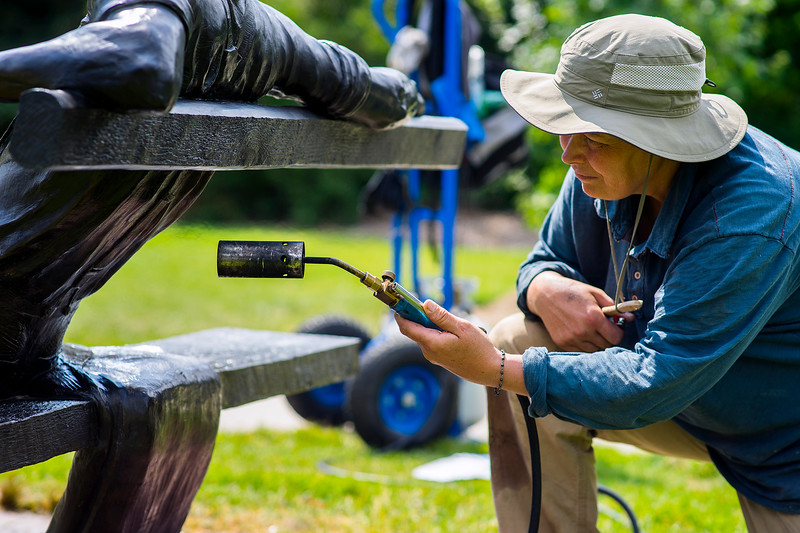 Jo DeDecker blasts a bronze sculpture with heat at the Benson Sculpture Garden in Loveland on July 28, 2016. The bronze sculptures must be heated to soften the existing wax and allow for application of a new wax layer that will keep the artwork clean.<br /> <br /> Photo by Michael Ortiz/Loveland Reporter-Herald
