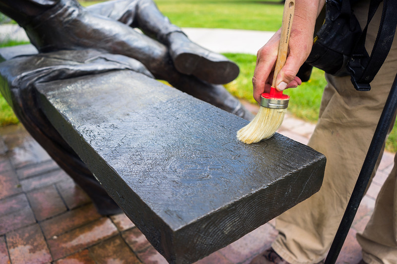 Jo DeDecker waxes a bronze sculpture in the Benson Sculpture Garden in Loveland on July 28, 2016. The wax used to clean the sculpture is unique in the mixture of wax and mineral spirits that allows DeDecker to clean and apply wax at the same time. <br /> <br /> Photo by Michael Ortiz/ Loveland Reporter-Herald