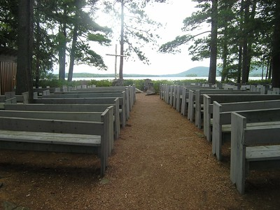 As you enter this outdoor chapel, you observe pews with a huge white birch cross in the front, framed by Squam Lake and Mt. Chocorua.