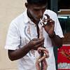 Lighting cigarette with smoldering coir rope mounted at a store, Negombo, Sri Lanka