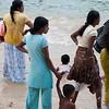 Fully-clothed women watch their children play at beach, Unawatuna, Sri Lanka