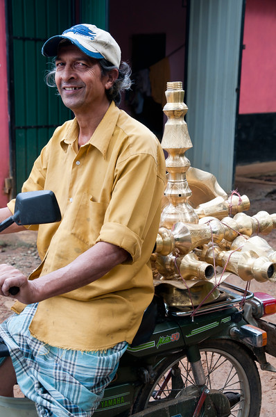 Man transports brassware made in his home shop, Handessa, Kandy, Sri Lanka
