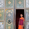 Young monk stands in ornate doorway at Lankatilake Temple.