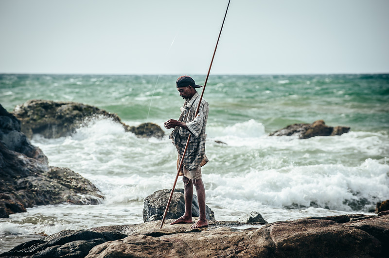 A fisherman hooks his bait, Induwura, Sri Lanka
