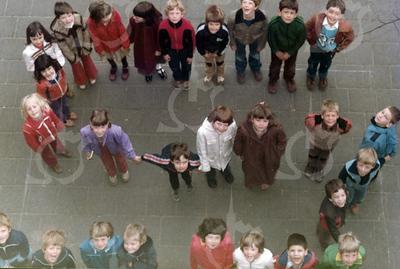 """W001<br /> Fotoboek, aangeboden door het team van de St. Annaschool b.g.v. het afscheidsfeest van Meneer Vermeulen (""""Wim"""" voor sommigen) op 25 juni 1980. <br /> Hij zou daarna vertrekken naar Waalre bij Eindhoven om er directeur van een grote basisschool te worden. De school telde toen 12 klassen. Precies genoeg om elke klas een letter te laten vormen van """"St.Annaschool"""". De foto's werden genomen vanuit het """"kaartenkamertje"""", achteraan de gang boven."""