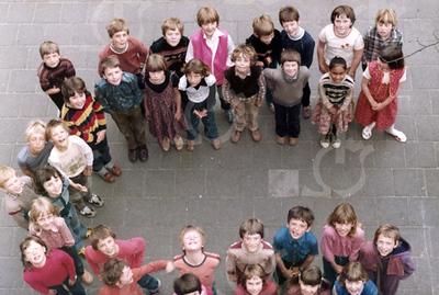 """W008<br /> De school telde toen 12 klassen. Precies genoeg om elke klas een letter te laten vormen van """"St.Annaschool"""". De foto's werden genomen vanuit het """"kaartenkamertje"""", achteraan de gang boven."""