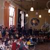 W039<br /> Maandopening in de filmzaal. Die zaal bestaat uit twee aaneen gevoegde klaslokalen. Op de achtermuur drie fraaie mozaïeken, ontworpen en gemaakt door Wim Vermeulen.